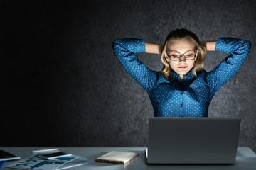 Attractive blonde working on laptop in dark office. Mixed media