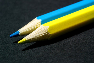 Photo of sharpened yellow and blue pencils close-up lying in a row on a dark background