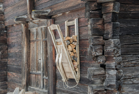Wood carrier backpack hanging on old wooden wall in small village in swiss mountains