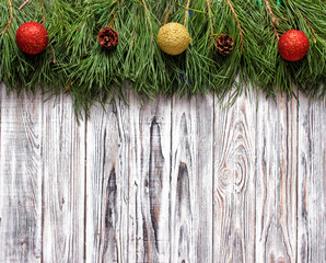 white wooden background with spruce branches and Christmas balls, place for the inscription, blank for inscription, the New Year holidays