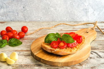 Fresh tomato bruschetta on wooden background, with basil and garlic