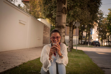 Young woman with smart phone laughing on the street .