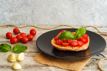 Bruschetta with fresh tomato, basil and garlic on black dish