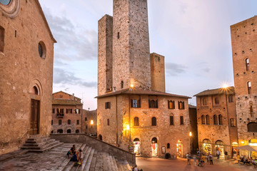 Evening with relaxing people under brick towers of ancient town of Tuscany