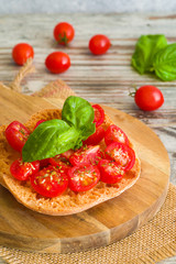 Fresh tomato bruschetta with basil on wooden background.