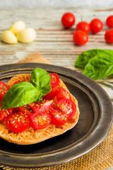 Fresh tomato bruschetta with fresh basil and garlic on rustic dish
