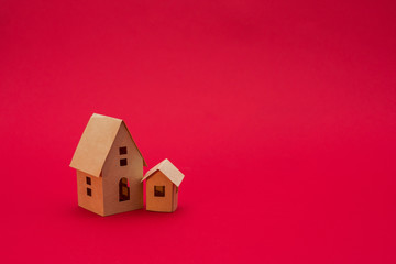 two paper houses, red background with copy space, for advertising, side view, close up