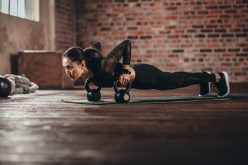 Fit female doing intense core workout in gym