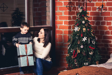 Mother gives gift to her son for Christmas.