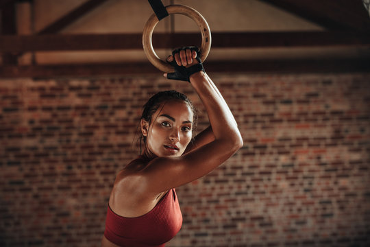 Sporty woman exercising with gymnastic rings at gym
