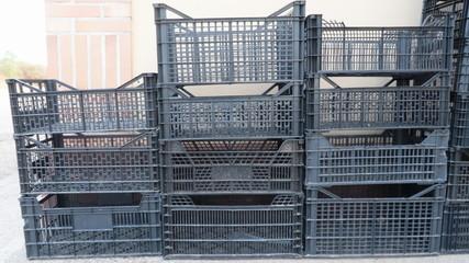 Cajas de plástico vacías negras usadas para  almacenaje de frutas, vegetales y otros alimentos apiladas o almacenadas para reciclaje