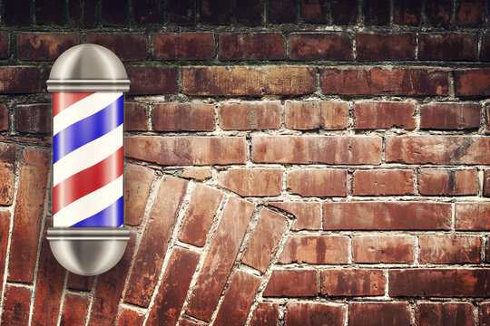 Barber pole on the background of the old brick wall. Concept Barber Shop.