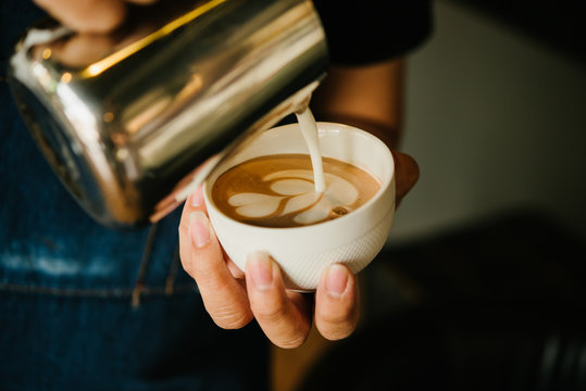 Barista pouring milk in coffee cup .