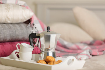 Breakfast in bed. On a white wicker tray there is a coffee maker, coffee cups and croissants.