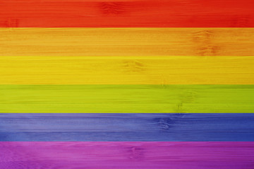 LGBT flag colors over wooden textured background. Gay pride