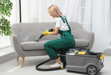 Female janitor removing dirt from sofa with upholstery cleaner in room