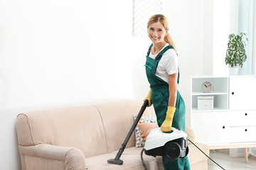 Female janitor removing dirt from sofa with steam cleaner in room