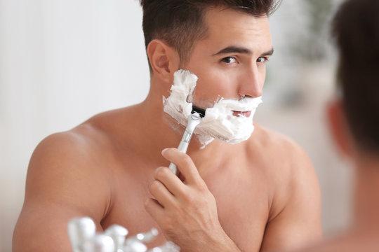 Young man shaving near mirror in bathroom