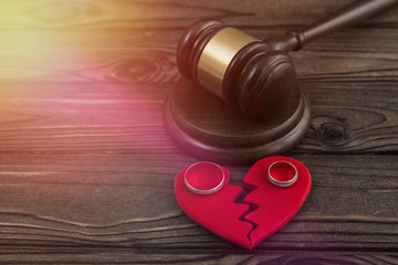 a judge's hammer, a heart, a pair of wedding rings against the background of a wooden table. divorce, family law.