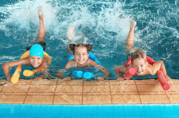 Foto auf Gartenposter Gymnastik Little kids with swimming noodles in indoor pool