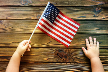 American flag in the hands of a child on a wooden background. patriotism, the day of independence.