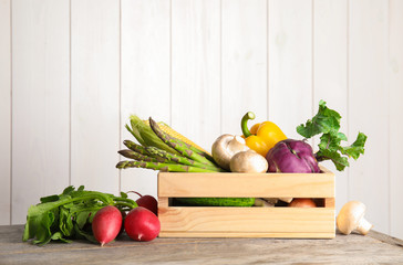 Crate with assortment of fresh vegetables on table against light background. Space for text