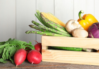 Crate with assortment of fresh vegetables on table against light background