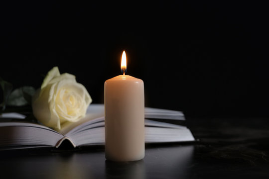 Burning candle, book and white rose on table in darkness, space for text. Funeral symbol
