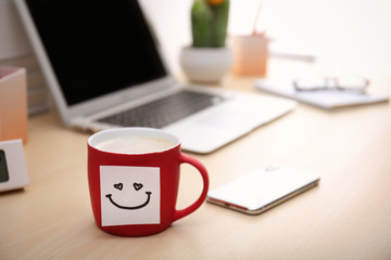 Sticky note with funny face attached to cup of coffee on office table. Space for text