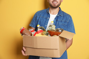 Young man holding box with donations on color background