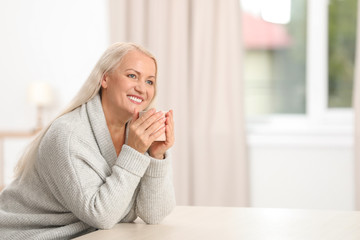 Portrait of beautiful older woman with cup of tea sitting at table indoors. Space for text