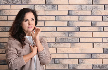 Portrait of beautiful older woman against brick wall with space for text