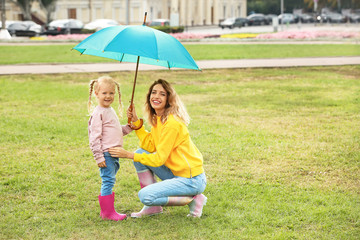 Happy mother and daughter with umbrella in park