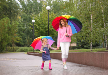 Happy mother and daughter with bright umbrellas walking in park