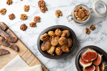 Flat lay composition with walnuts, fresh and dried figs on marble background
