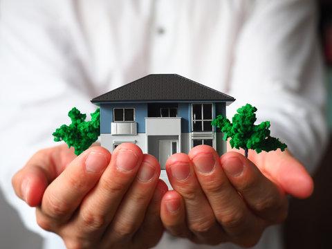 両手で家の模型を持つ男性