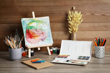 Easel with abstract painting and set of professional art supplies on table against wooden background