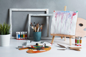 Easel with abstract painting and set of professional art supplies on table against grey background