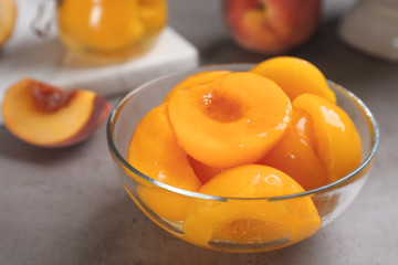 Glass bowl with conserved peach halves on grey table