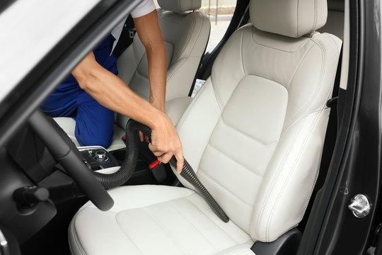 Man using vacuum cleaner in auto, closeup. Car wash