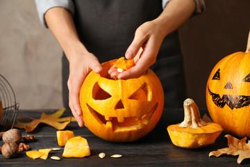 Woman making Halloween pumpkin head jack lantern on wooden table, closeup