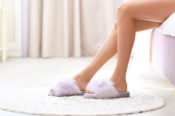 Closeup view of woman in fuzzy slippers sitting on bed. Floor heating