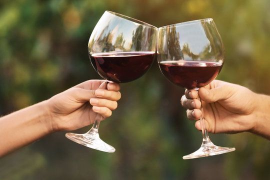 Couple with glasses of red wine outdoors, closeup