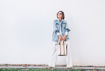 Wall Mural - Woman in elegant outfit with oversize denim jacket