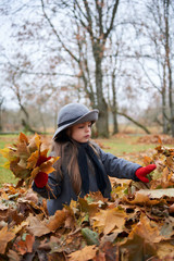 The girl plays with yellow leaves.