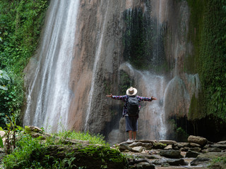 Senior man with backpacks enjoying waterfall raised hands Travel Lifestyle and success concept