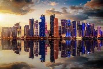 Die urbane Skyline von Doha in Katar bei Sonnenuntergang mit Reflektionen in der Bucht