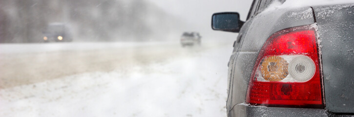 Car on winter road in a snowstorm and bad visibility, border design panoramic banner