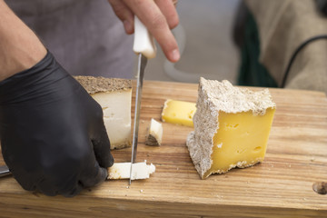 A man is cutting cheese.
