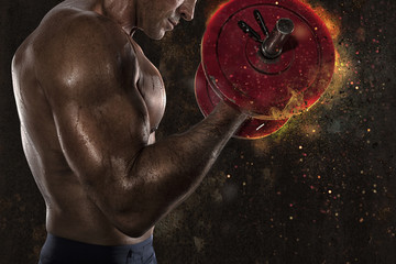 Athletic man training biceps at the gym with fire effect